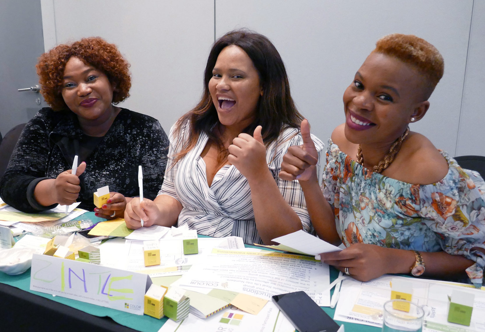 3 women holding thumbs up in a workshop